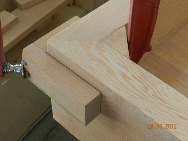Method for clamping mitered corners of workbench top using triangular section cut offs.