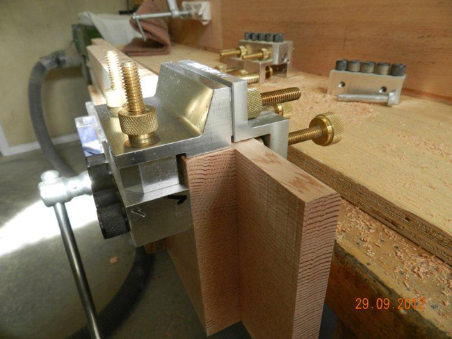 Dowelmax dowel jig in face joint configuration clamped to workbench leg.