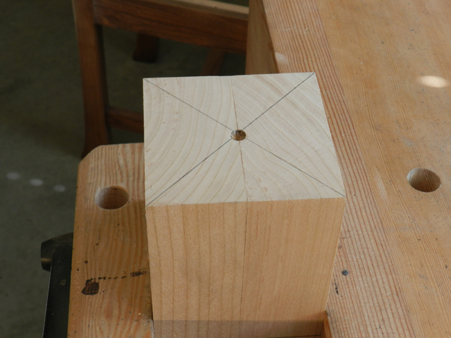 Marking the lathe center on the table leg workpiece.