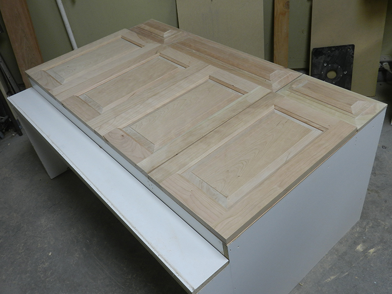 Four bathroom cabinet raised panel doors and drawer panels laid out on top of the original carcass.