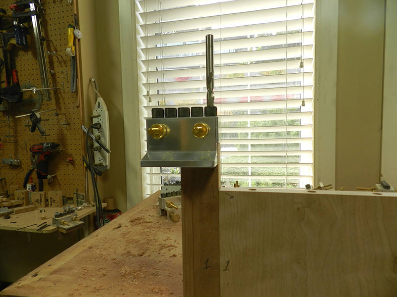 Dowelmax dowel jig aligned on adjacent plant stand top plate perimeter rail to drill bores before cutting the miter.