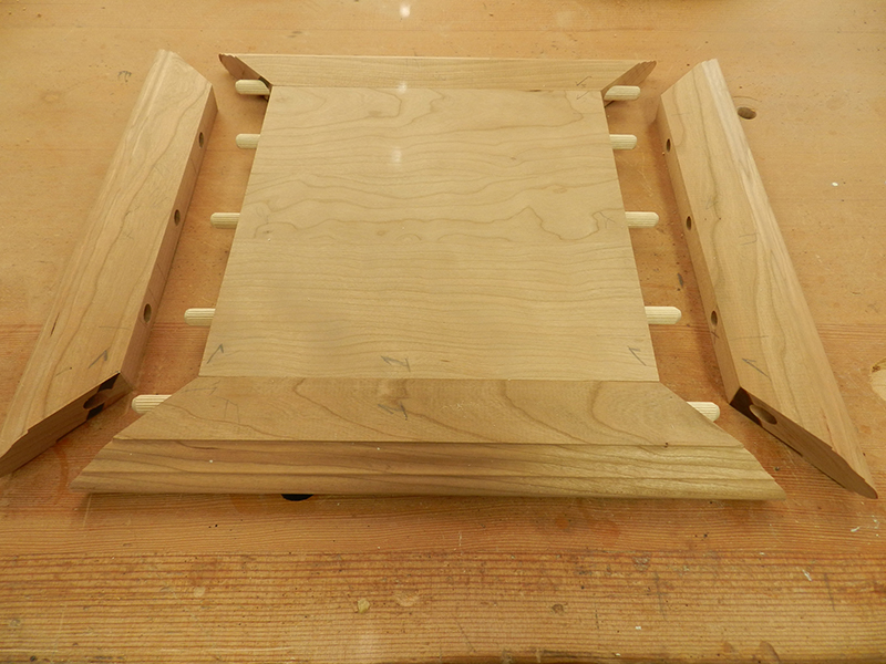 The plant stand top plate and mitered rails partially fitted to show the orientation of the dowel connections.