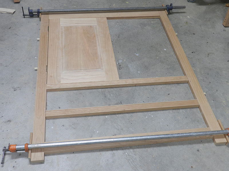 photo of the rails, stiles and one of the raised panel door components used to build the armoire frame assembly front section dry fitted to show the location of the door hinges