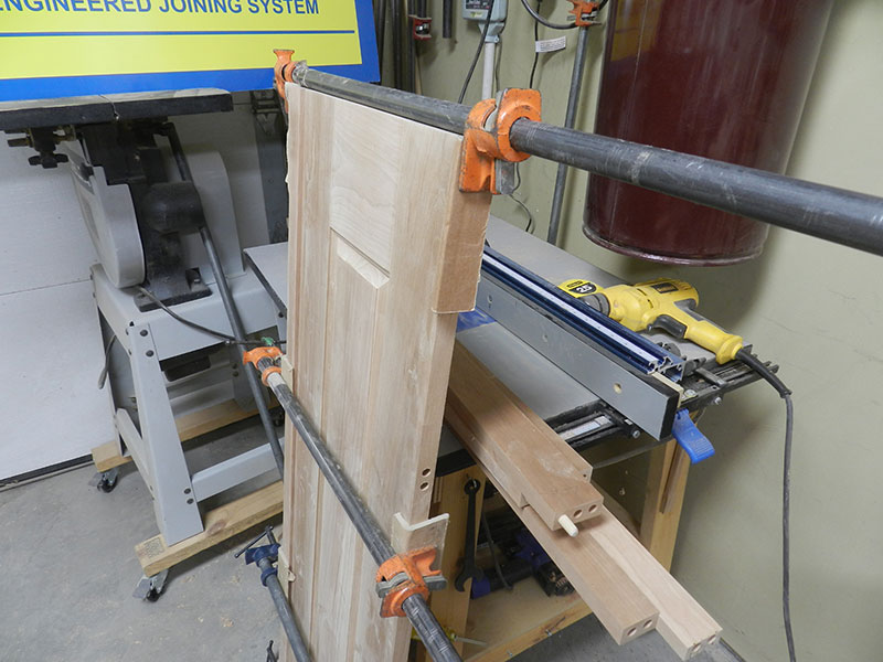 photo of raised panel assembly and one of the corner posts used to build the armoire frame assembly side section shown glued and clamped together