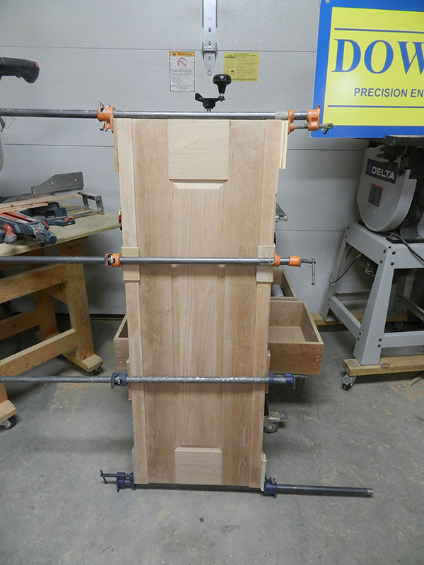 photo of raised panel assembly and both corner posts used to build the armoire frame assembly side section shown glued and clamped together