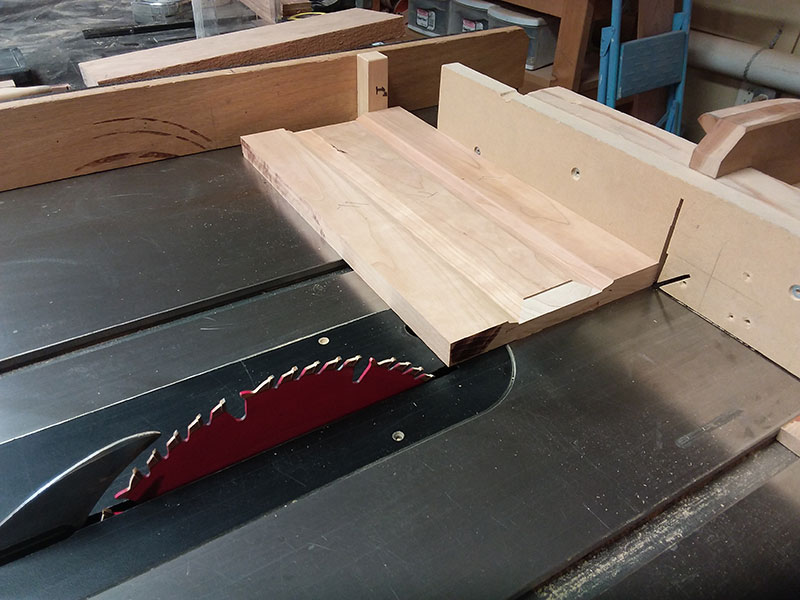 photo of trimming the rails and center panel used to build the bedside table frame side sections to length in the table saw